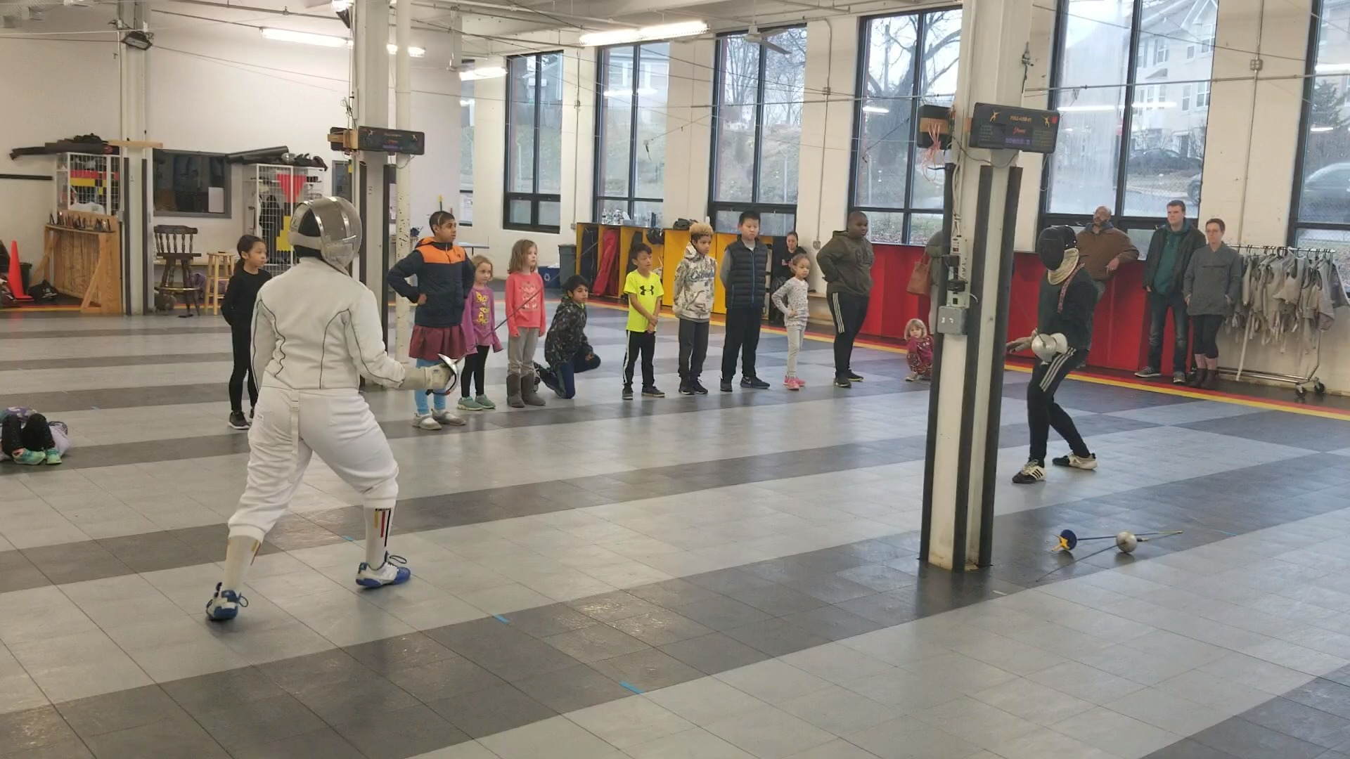 Afwé Griffin facilitates a fencing demonstration with coach James Miller